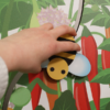 Hand moving the bee cutout along its track on the Buzz about Bees display