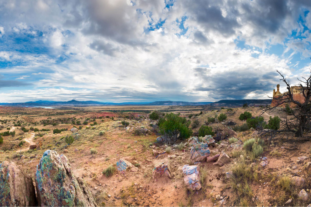 Promo image for article on New Mexico ag, showing mountains, rocks, sagebrush, and scattered clouds