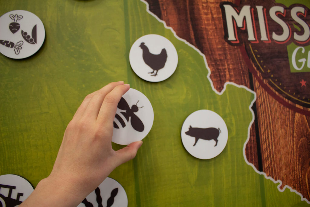 Photo showing someone placing a magnet on the map incorporated into the Agricultural Diversity Display
