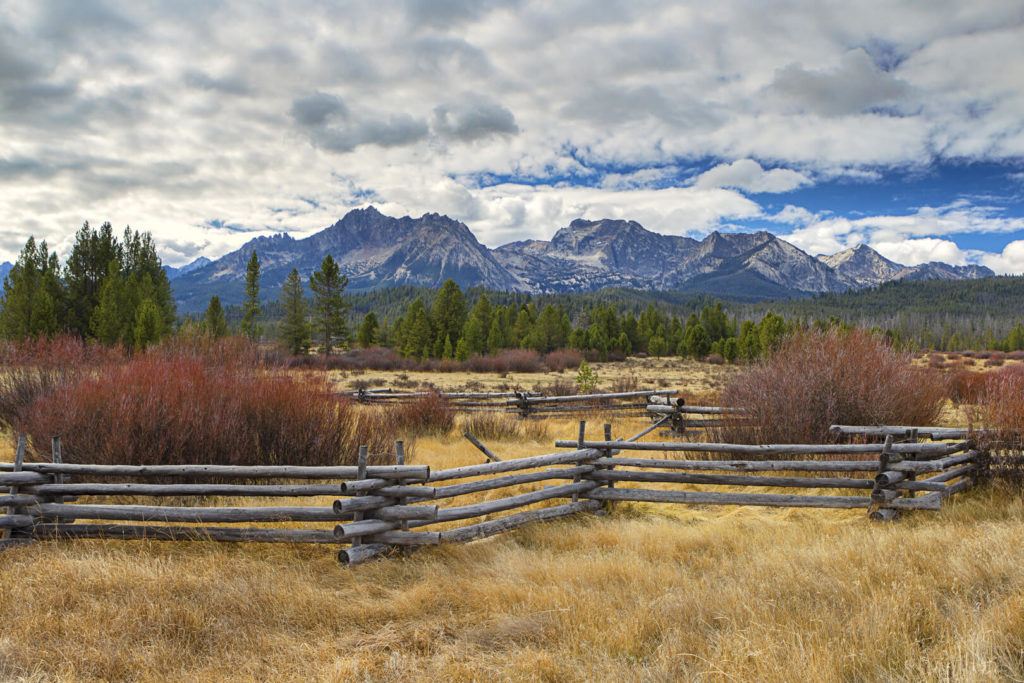 Split-rail fence with pasture, evergreen trees, and Idaho's Sawtooth mountains in the background