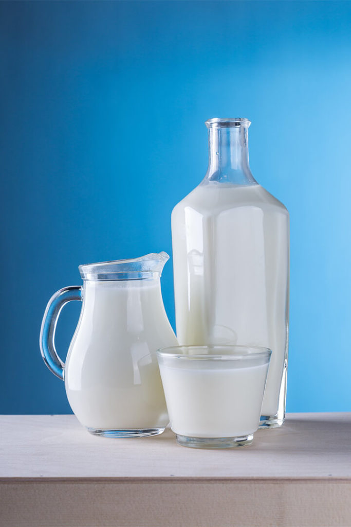 Three glass bottles of milk against blue background; used in an article about the rbst controversy