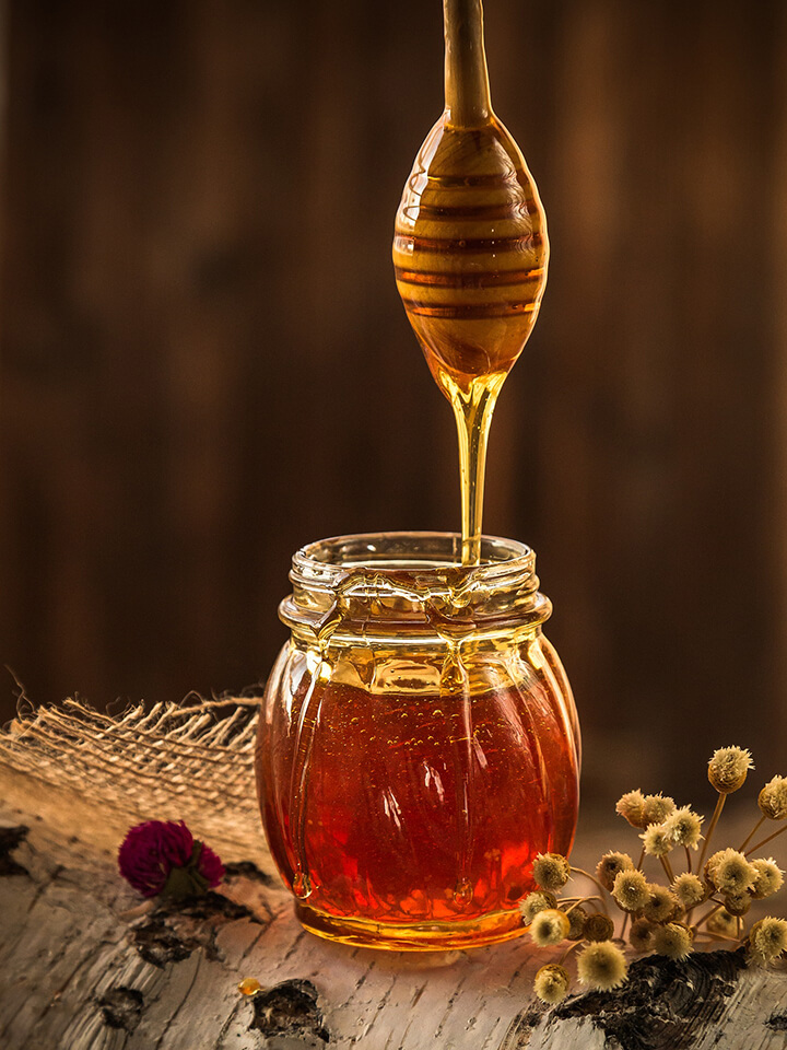 Honey drizzling into a jar
