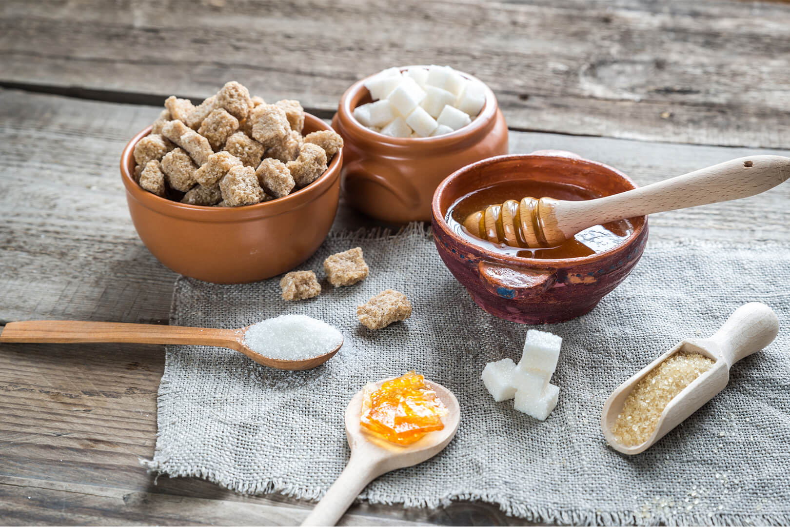 Bowls of brown sugar, white sugar, and honey; used for article on sweeteners