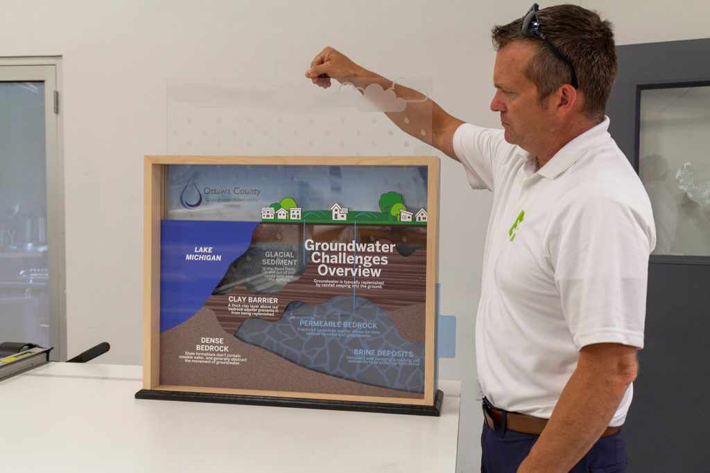 A man lifts the top panel on the groundwater challenges display