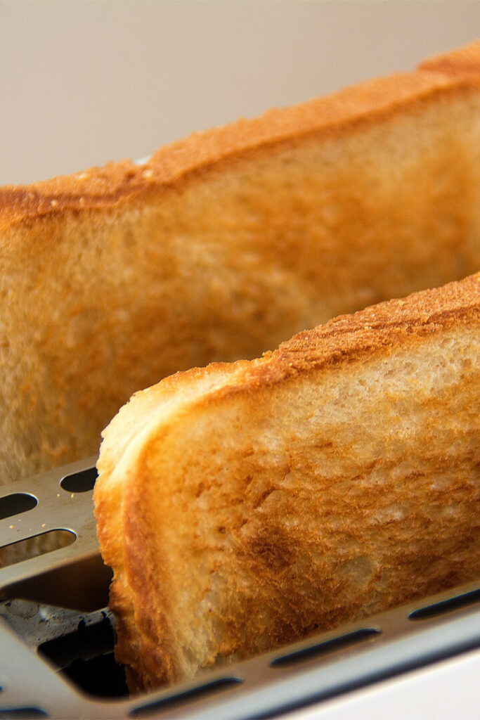 Two pieces of white bread in a toaster