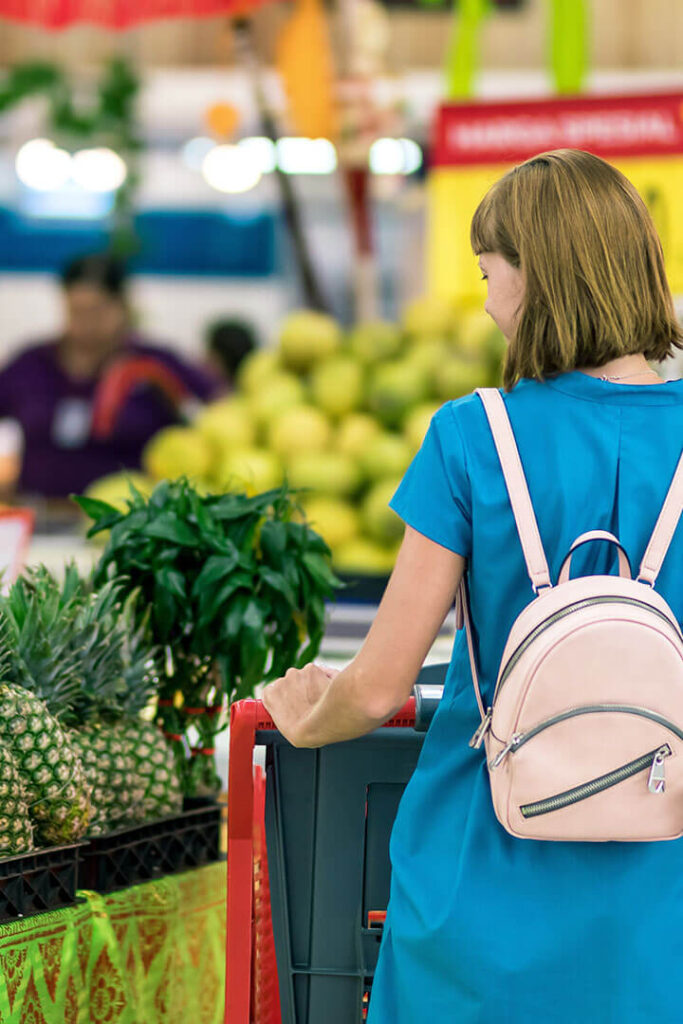 Young woman with a shopping cart in a grocery store looking at produce