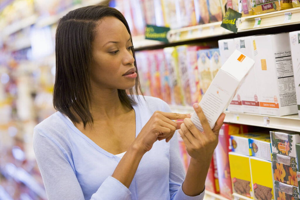 Woman examines a nutrition label in a grocery store