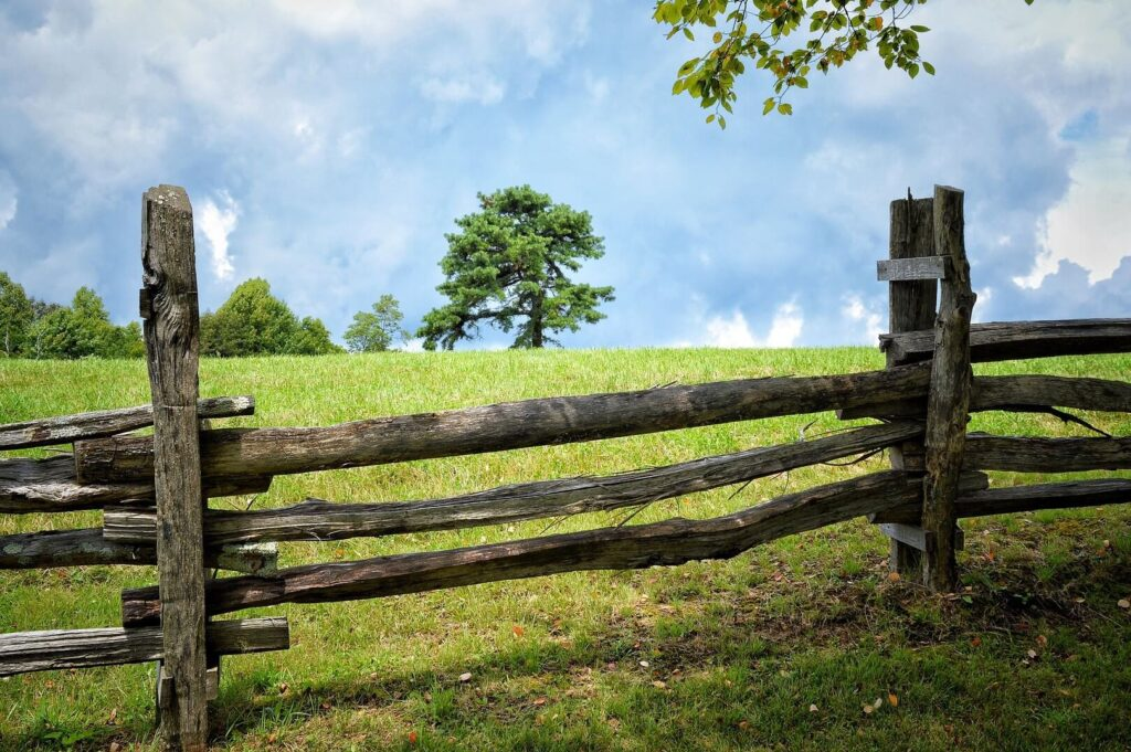 Split rail fence in front of a grassy field