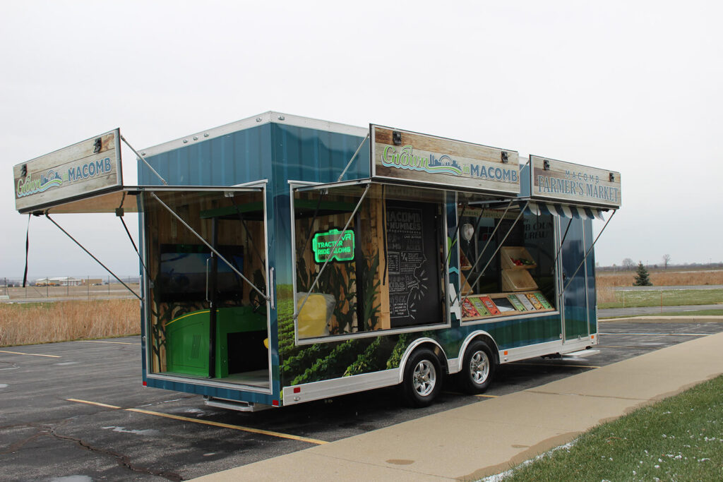 Macomb County exhibit trailer with panels pulled up to show displays inside