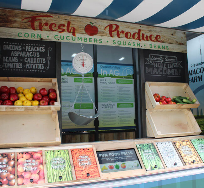 Photo op made to look like a farmers market stand in an exhibit trailer
