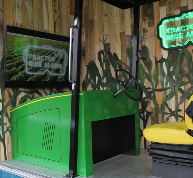 Angled view of virtual reality tractor experience, showing the attract screen and tractor seat