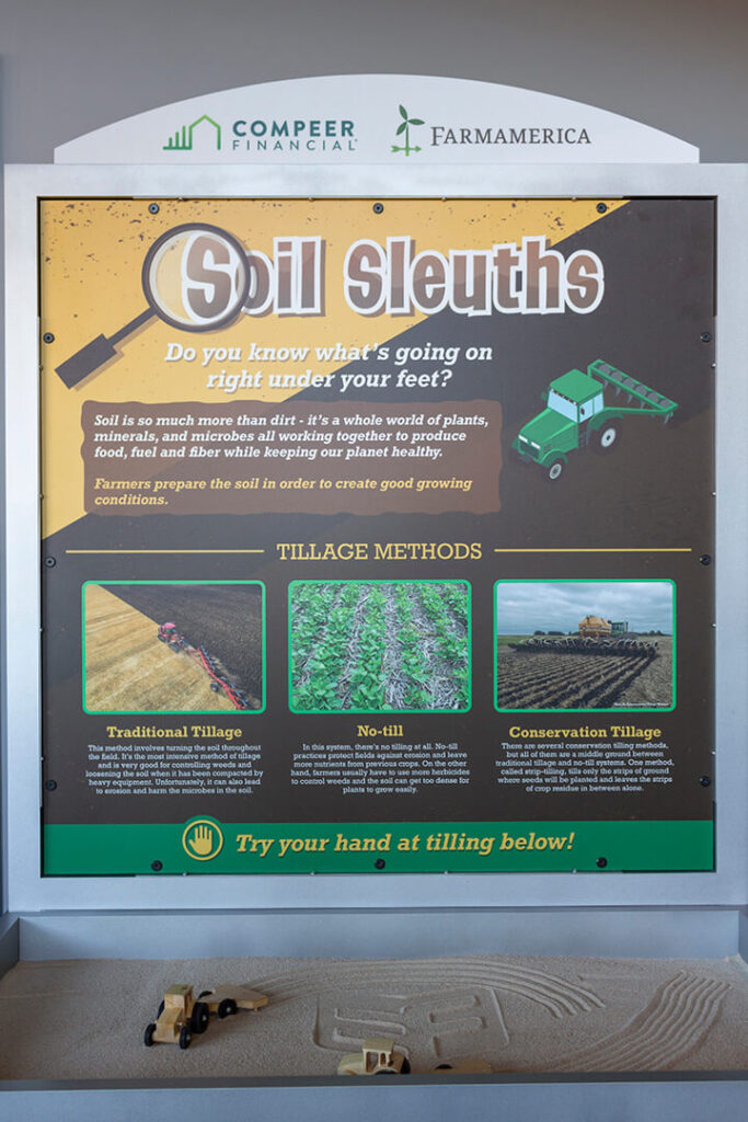 Front of display showing graphic panel about tillage methods and sandbox tray with toy tractors