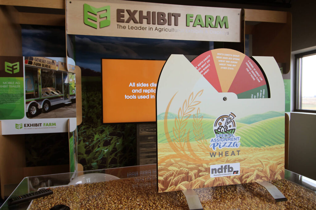 Standup display about wheat facts sitting in front of TV and other Exhibit Farm products