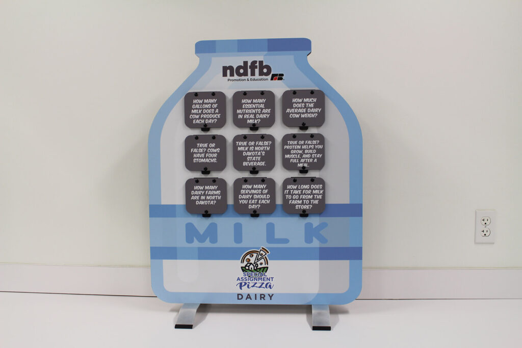 Tabletop milk bottle display with dairy facts