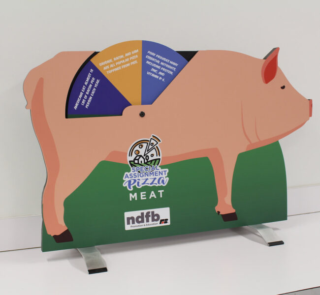 Tabletop pig-shaped display with wheel of facts about pig products