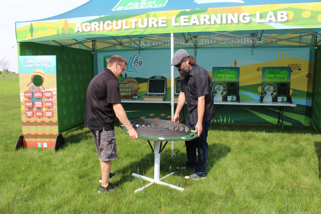 Two men playing the farm maze game in front of an exhibit tent
