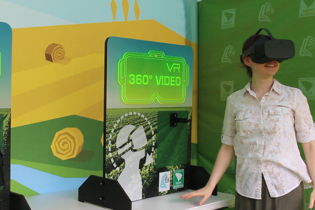 A woman standing next to the virtual reality station smiling while looking through VR goggles