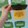 Hand lifting a flip-up door on the renewable fuels standup to show answer to trivia question