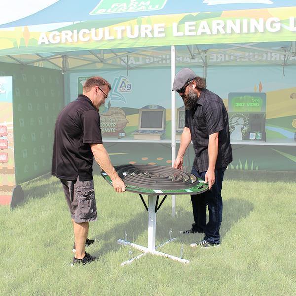 Two men playing the corn maze tilt table game