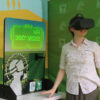 A woman standing next to the display station and wearing the VR headset