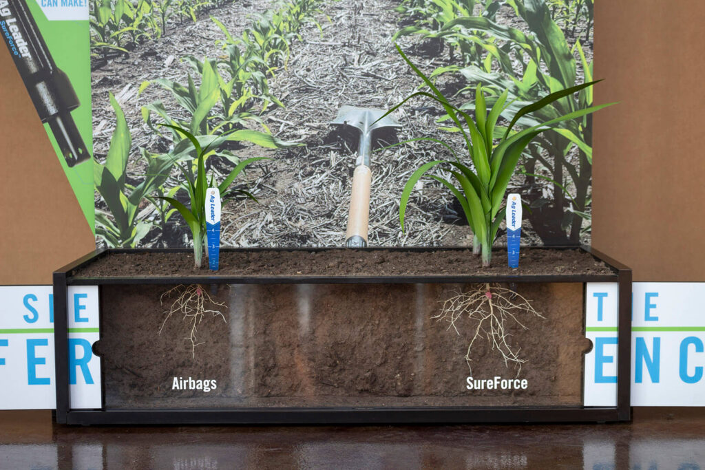 Planting technology display with the panels open to show the roots of the artificial corn plants