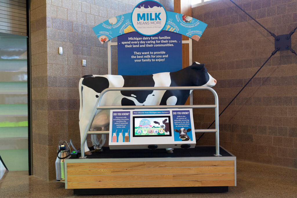 Milking cow display with cow sculpture and video monitor.