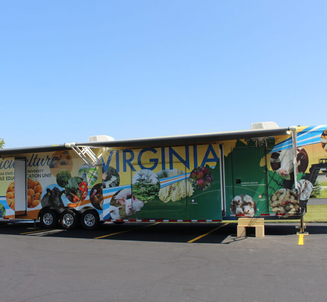 VSU agricultural exhibit trailer with sections slid out and sunshades put up.